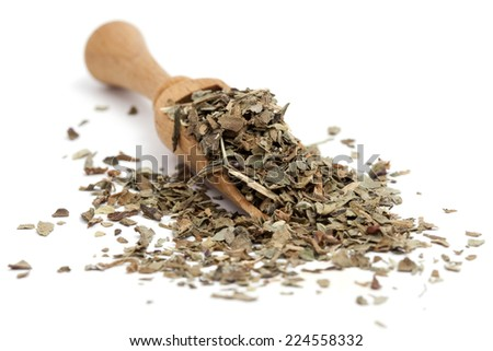 Dried basil in a wooden spoon