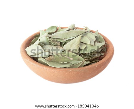 Dried bay leaves in a clay bowl isolated on white background