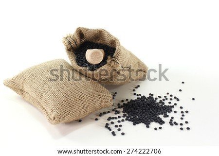 dried beluga lentils in sacks with bushels on a light background