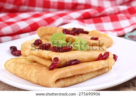 Dried berries and thin pancakes. Delicious Breakfast, lunch. To eat pancakes. A coffee shop, restaurant. Recipe pancakes. Closeup. Pancakes with mint and cranberries. Fried pancakes. Crepes for lunch. - stock photo