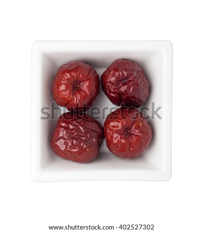 Dried big red jujubes in a square bowl isolated on white background