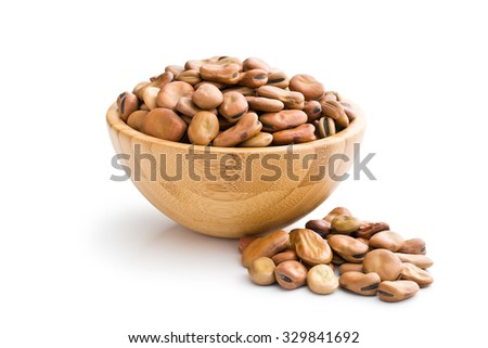 dried broad beans in wooden bowl on white background - stock photo
