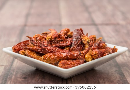 Dried cayenne pepper in a square bowl over wooden background - stock photo