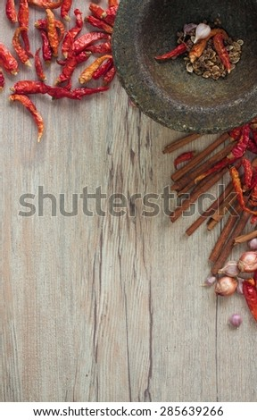Dried Chili and spices in a stone mortar on a wooden table. Can be used as background and texture. - stock photo