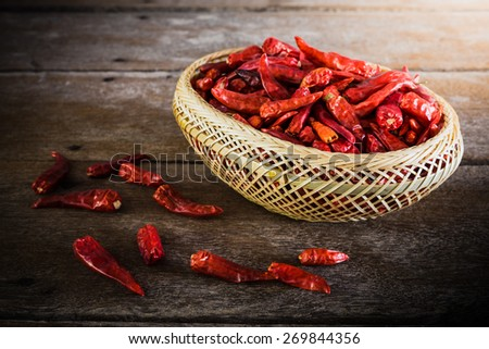 Dried Chili Peppers Bamboo Basket on wooden table. vintage tone - stock photo