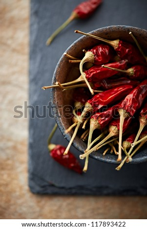 Dried chili peppers in a ceramic bowl - stock photo