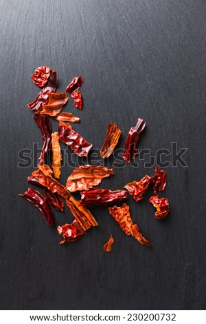 Dried chilly / chili flakes on black slate, top view - stock photo