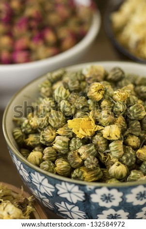 Dried Chrysanthemums Buds w Rose Buds in background; Non sharpened file - stock photo