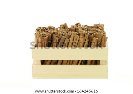 Dried cinnamon sticks in a wooden crate. On a white background. - stock photo