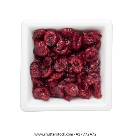Dried cranberries in a square bowl isolated on white background - stock photo