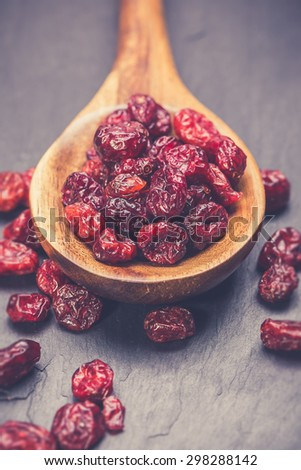 dried cranberries in a wooden spoon. fruit full of vitamin c. - stock photo