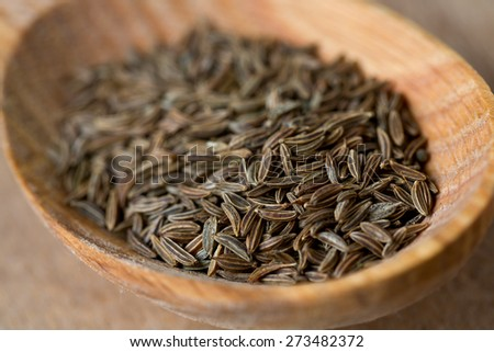 dried cumin on wooden surface