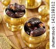 Dried date palm fruits or kurma, ramadan food which eaten in fasting month. Pile of fresh dried date fruits in golden metal bowl. - stock photo