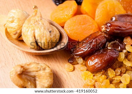 dried dates,dried figs in wooden spoon, raisins, prunes, dried apricots on a wooden board - stock photo