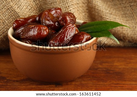 Dried dates in bowl on table on sackcloth background - stock photo