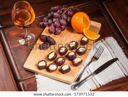 Dried dates stuffed with cheese served with white wine - stock photo