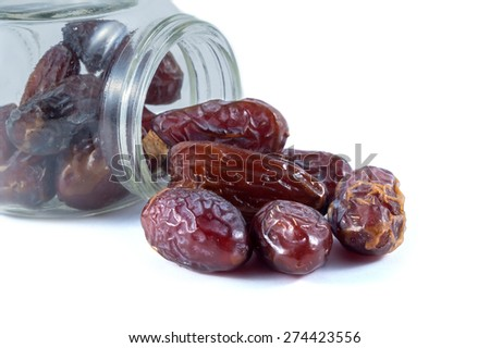 Dried dates with a glass container on white background