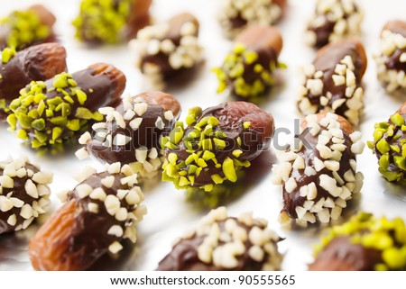 Dried dates with chocolate cover and almond and pistachio slivers on aluminum foil - stock photo