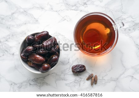 Dried dates with cup of tea on marble table. Traditional arabic food. Ramadan event. Top view - stock photo