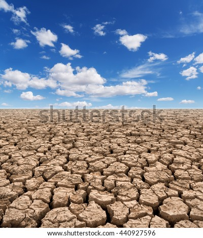Dried earth,cracked earth,Drought land against a blue sky with clouds - stock photo