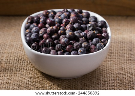 dried elderberries in small white bowl on linen, cloth background - stock photo