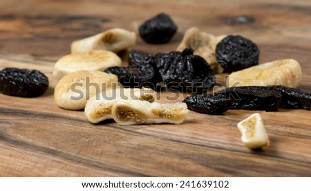 Dried figs and plums on a wooden table - stock photo