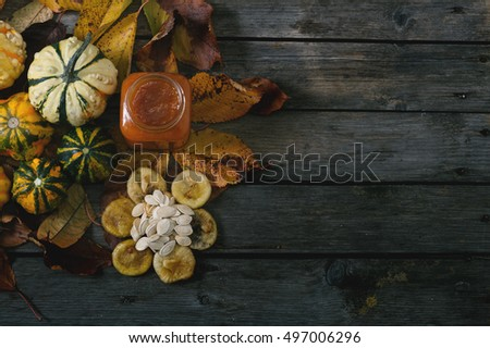 Dried figs, pumpkin seeds, pumpkins, pumpkin jam and sugar on vintage table. Selective focus and small depth of field.