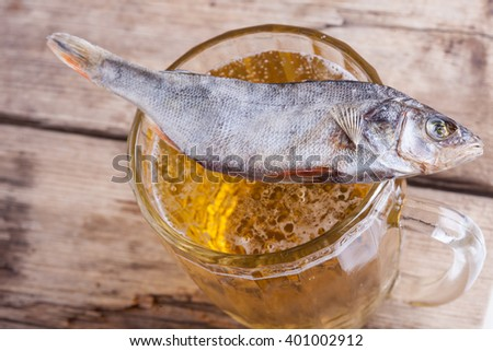dried fish with beer on the table background