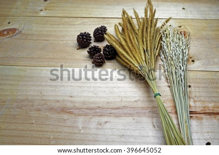 dried flower , rice and pine cones on wooden floor