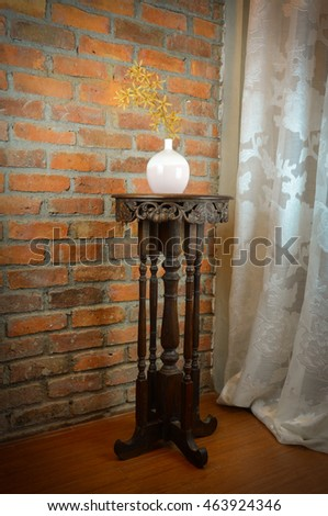 Dried flower vase on the table, antique wood carving. The rear wall of orange brick with cement as a binder. Surface roughness And a long white curtains from the top down to the bottom trim.