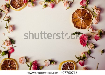 dried flowers dried roses with round slices of lemon are laid out in a frame shape with free space