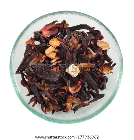 Dried fruit tea with hibiscus on glass saucer isolated on white background.