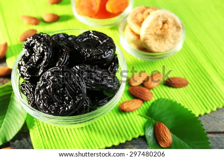 Dried fruits and almonds with leaves on green napkin, closeup - stock photo