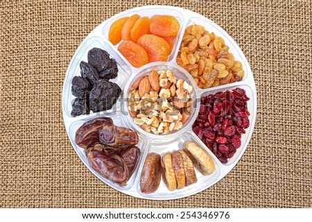 Dried fruits and nuts in plastic container for food storage. Raisin, cranberry, fig, plum, date, apricot fruits, walnuts and  almonds isolated on the canvas texture background - stock photo