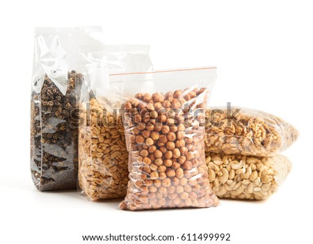 Dried fruits and nuts in transparent package over white from left to right: dried mulberry, roasted and salted peanuts, hazelnuts, walnut and cashew on the bottom