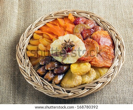 Dried fruits collection in braided basket on brown burlap .
