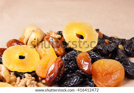 dried fruits, dried pineapple, dried figs, walnuts, prunes, figs, dried apricots on a paper background - stock photo