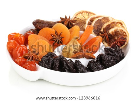 Dried fruits with anise stars on plate isolated on white - stock photo