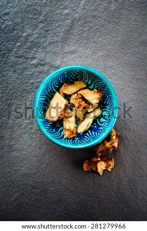 Dried Galangal Root in Authentic Oriental Bowl on Stone Background. Top View. Selective Focus. - stock photo