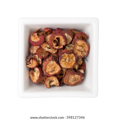 Dried hawthorn fruits in a square bowl isolated on white background - stock photo