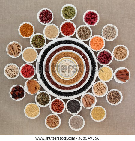Dried health food in china bowls forming an abstract wheel design over hessian background. Foods high in minerals, vitamins, antioxidants and dietary fiber. - stock photo