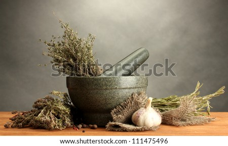 dried herbs in mortar and vegetables, on wooden table on grey background - stock photo