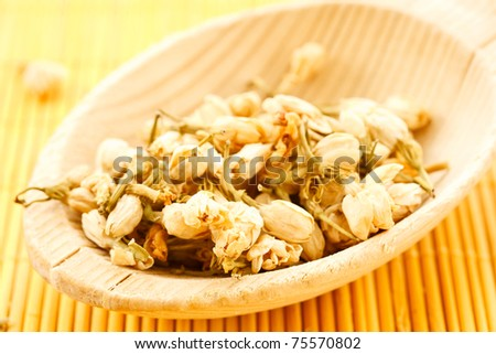 Dried jasmine in a wooden spoon