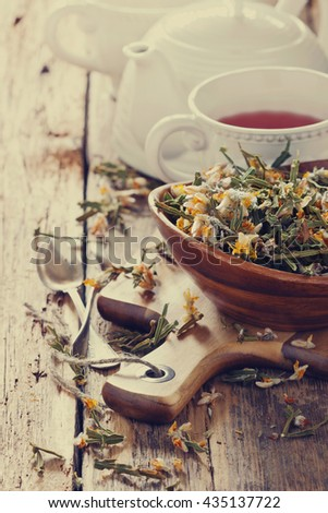 Dried medicinal herbs  and helpful  tea on a wooden table.( Carqueja and Genista Tridentata). Alternative treatment . Selective focus. Toned image