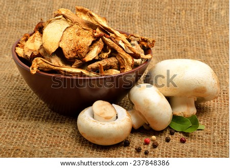 Dried mushrooms in the bawl, ceps and raw champignons on the sacking background - stock photo