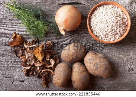 Dried mushrooms, potato, onion, dill and grain in a bowl on a old wooden board - stock photo