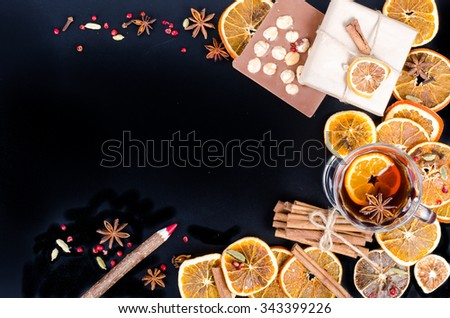 Dried oranges, cinnamon, cloves, cardamom, handmade milk chocolate with nuts, wooden pencil, list of paper on black background. Christmas, New Year and winter. Free space for your text. - stock photo