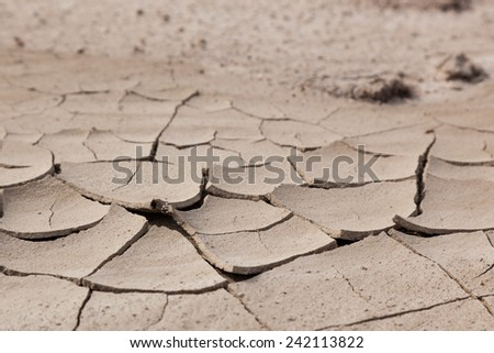 Dried out mud cracks into pieces and lifts on the edges from drought conditions in Badlands National Park, South Dakota. - stock photo