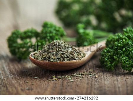 dried parsley in wooden spoon on old wooden - stock photo