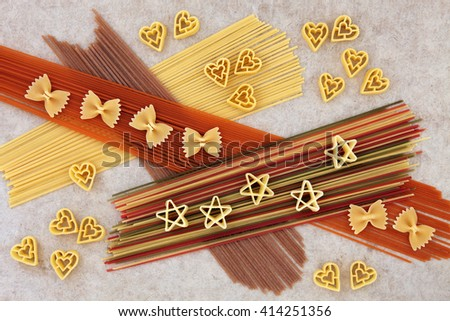 Dried pasta spaghetti food abstract background over natural hemp paper. Coloured varieties dyed with beetroot, tomato, carrot and spinach food colouring. - stock photo